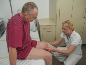 Fyzioterapeutka bandážuje pahýl.